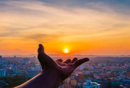 夕日と背景の都市を持っている手。