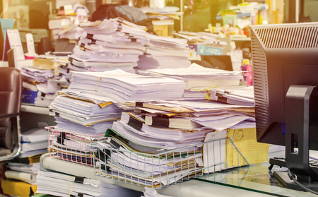 unorganized: Pile of documents on desk stack up high waiting to be managed. Stock Photo