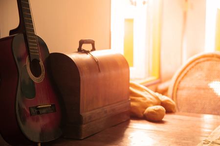 acoustical: Acoustic guitar on wooden table with chest. Stock Photo