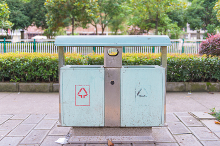 botes de basura: botes de basura en el parque al lado de la calzada.