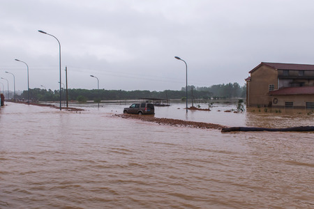 drowned: flooded road junction with a drowned car in china.