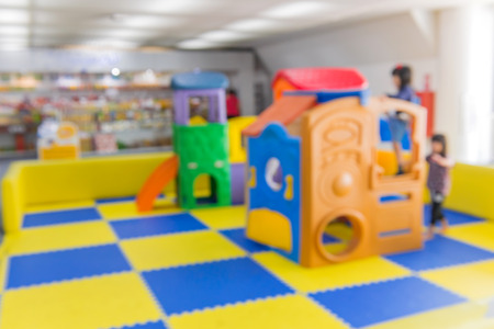 blurred image of children playground activities in hall.