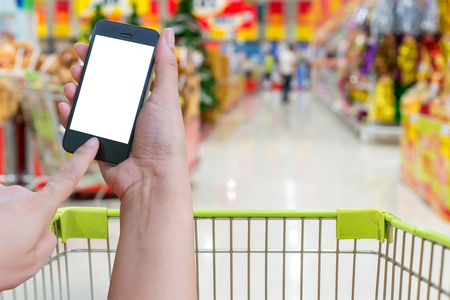 Woman hold and touch screen mobile phone while shopping in super market background.