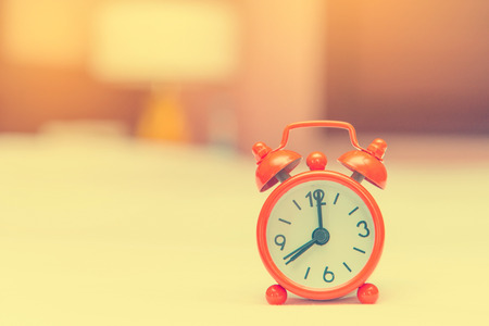 working hours: alarm clock on the bed in bedroom. Stock Photo