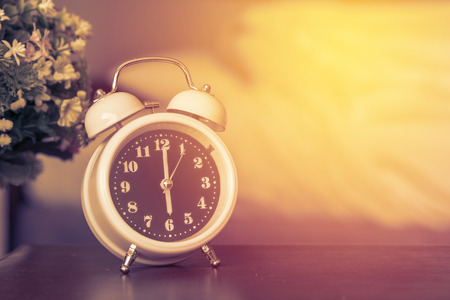 alarm clock on the bed in bedroom. Stock Photo