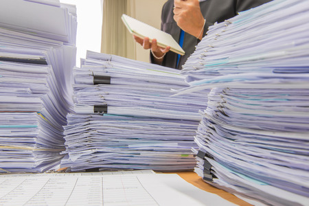 managed: documents on desk stack up high waiting to be managed Stock Photo