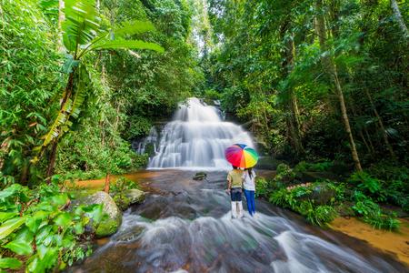 Couple with colorful umbrella standing in waterfall at phu tub berk mountain phetchabun, Thailand. (Mun Dang waterfalls) Stock Photo