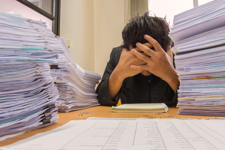 managed: documents on desk stack up high waiting to be managed. Stock Photo
