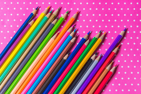 Color pencils isolated on Pink fabric background.