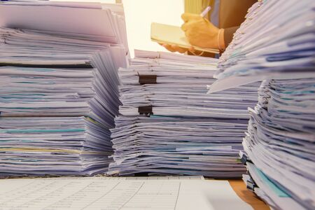 unorganized: documents on desk stack up high waiting to be managed. Stock Photo