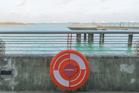 red Lifebuoy on railing by the sea. Stock Photo