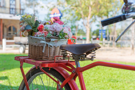 vintage bicycle equipped with basket of flowers in the garden.