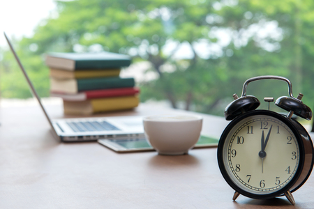 Retro alarm clock with cup of cappuccino on table in office, Coffee Break lunch time. Stock Photo