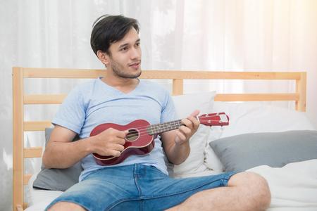 bedroom: Young man play ukulele song on bedroom.