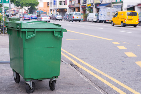 Green recycling bin container or garbage Trashcan on the street of city. Stock Photo