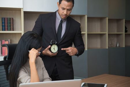 Upset woman being scolded by boss for working at office and Boss point to clock showing time for deadline job.