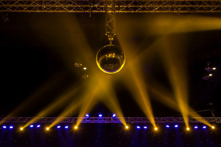 Disco ball with bright rays and night party background.