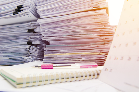 documents on desk stack up high waiting to be managed. Stock Photo