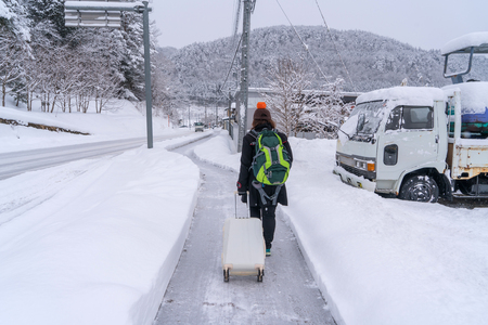 traveler with backpack and luggage walking on snow covered road in winter at Takayama Japan.