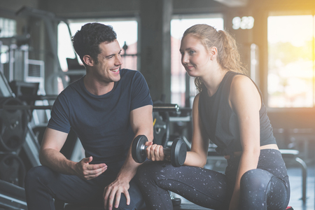 Young woman sitting on a stool with personal trainer, Trainer making fitness for female client at gym.