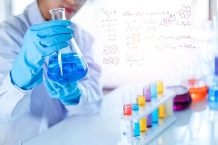 científico con equipo y experimentos científicos, cristalería de laboratorio que contiene líquido químico para investigar o analizar una muestra en un tubo de ensayo en el laboratorio.