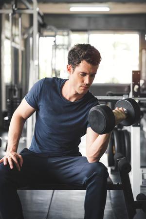 Gut aussehender Gewichtheber, der Bankdrücken mit Hanteln im Fitnessstudio trainiert.