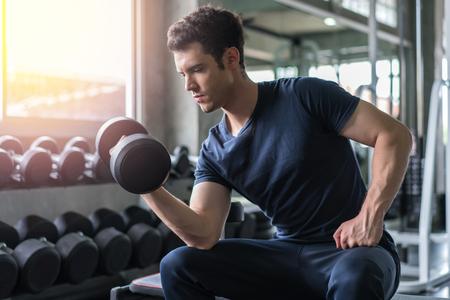 Gut aussehender Gewichtheber, der Bankdrücken mit Hanteln im Fitnessstudio trainiert. Standard-Bild