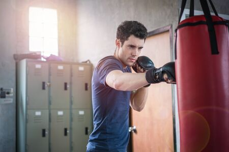 Handsome man in boxing gloves punching bags exercise in fitness gym.
