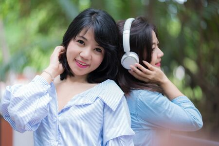 Two Young woman enjoying music in the garden listening to music with headphones.