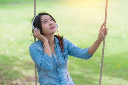 Young beautiful woman enjoying music in the garden listening to music with headphones.