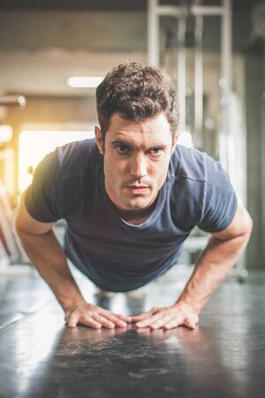 Handsome man and strong guy doing push ups exercise in fitness gym.