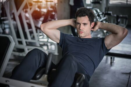 Handsome man exercising doing sit up abdominal exercise in gym. 写真素材