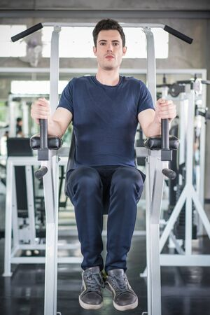 Handsome man exercising arm on machine builder muscles in fitness gym.