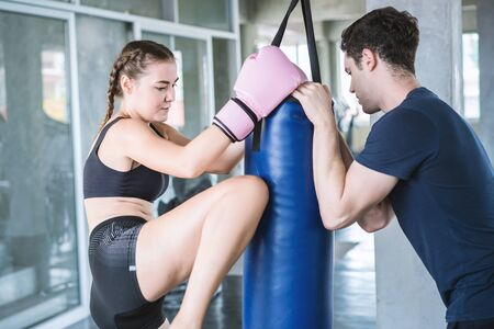 Handsome man beautiful sportswoman in boxing gloves punching bags exercise in fitness gym.