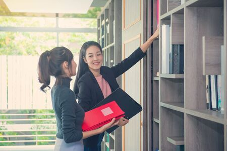 Business woman Searching for files in the cabinet or shelves with folders.