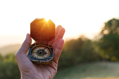 compass in mans hand with sunset nature background,  journey trip concept.