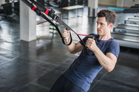 Athlete sporty man doing exercise with fitness straps to strengthen his abdominal muscle in gym.