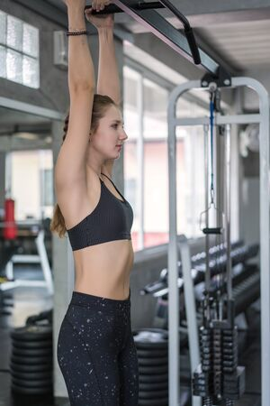 Beautiful woman exercise pull up bar in fitness gym at sport club. Reklamní fotografie