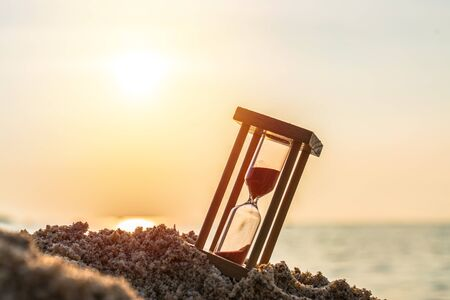 Time concept Hourglass on sandy beach in summer with sea background.