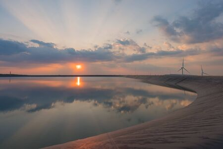 wind turbine generating electricity on dam catchment landscape energy transmission distribution equipment in natural environment