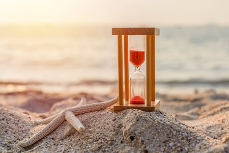 Time concept Hourglass and Starfish on sandy beach in summer with sea background.