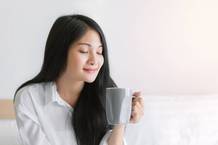 Beautiful young woman wake up and drinking coffee or tea in the morning at bedroom.