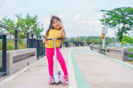 Little child girl to ride scooter in outdoor sports ground on sunny summer day. Active leisure and outdoor sport for children. Banque d'images