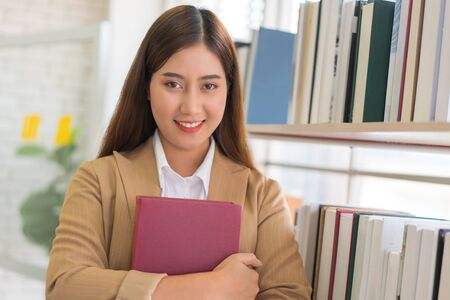 Business woman Searching files and and reading book in the cabinet or books shelves.