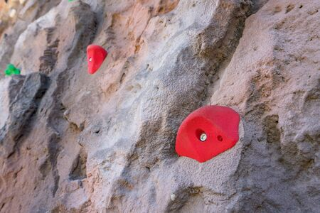 outdoor sports climbing stone wall with multiple grips simulating mountain climbing, extreme hobby concept.