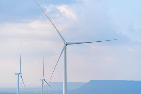 Wind turbine renewable energy source summer in forest mountains landscape energy transmission distribution equipment in natural environment.