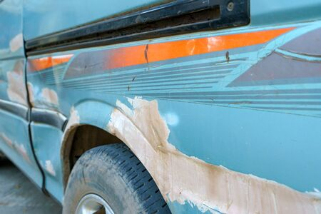 Car side is scratched and scraped with deep damage to the paint.