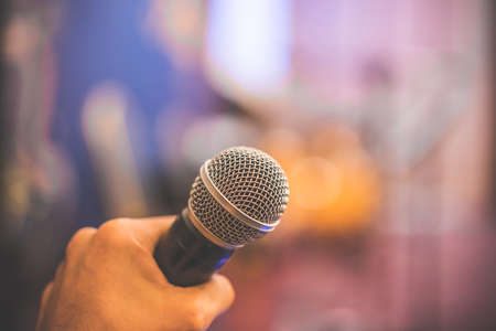 hand hold Microphone in meeting room for a conference.