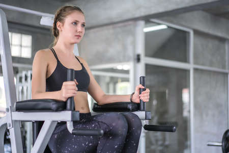 Athlete sporty woman exercising arm on machine builder muscles in fitness gym.