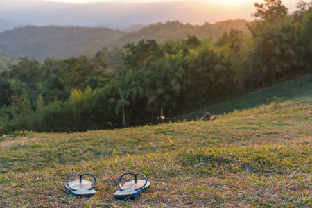 slippers placed on green lawn with background mountains at sunset.